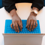 Aperson typing on a laptop with a blue keyboard